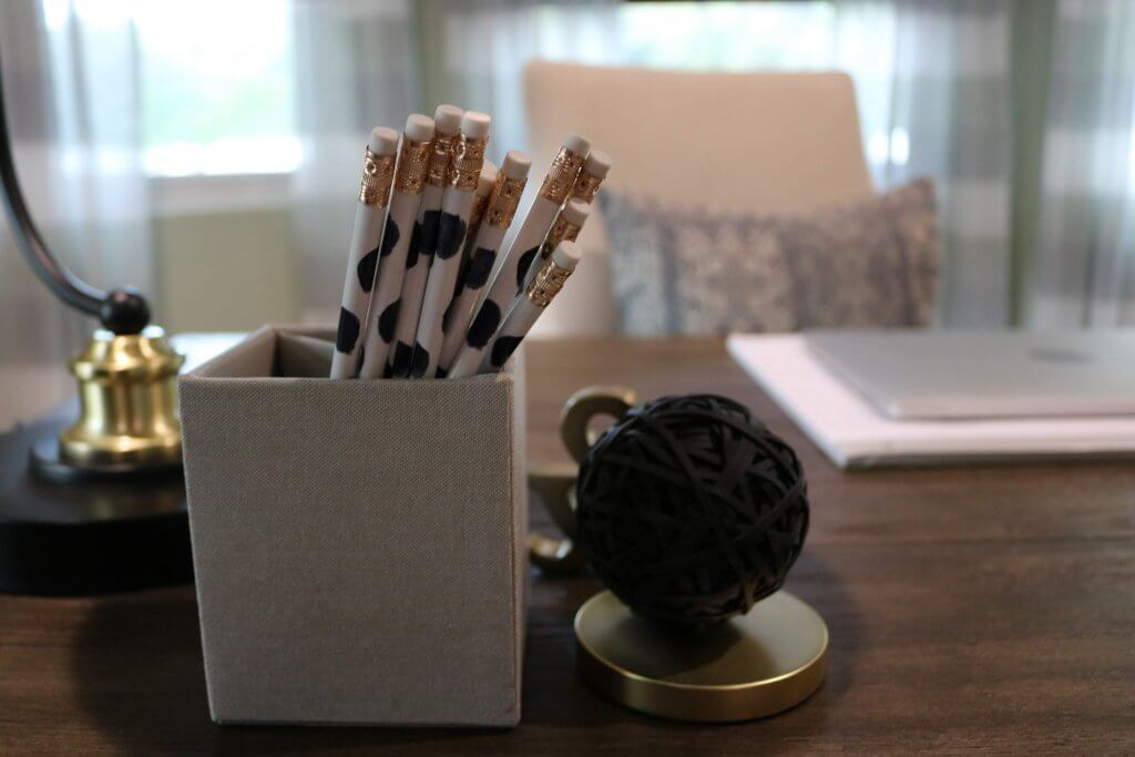 pencils in cup on desk with other decor