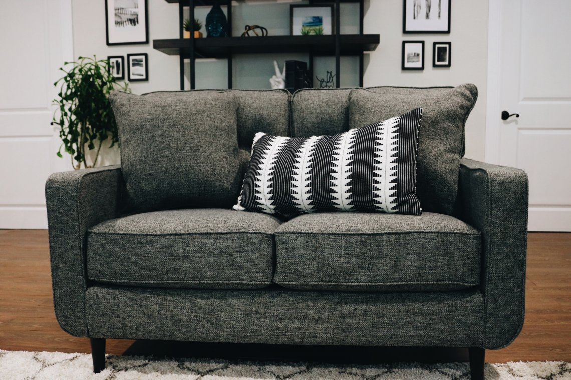 grey couch with black and white pillow