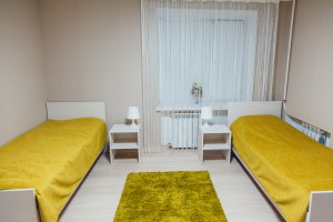 small dorm room with yellow sheets and rug