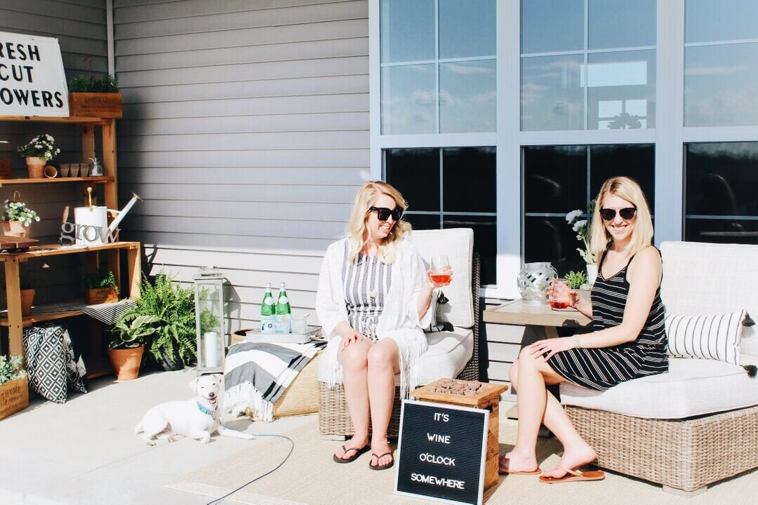 women on outdoor furniture with wine