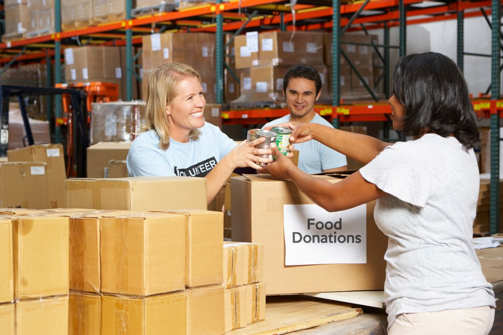 woman donating food to volunteers