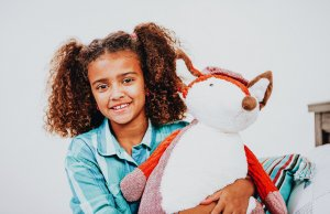 young girl on bed holding bear