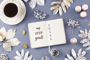 New Year goals list with candles, decor and coffee drink
