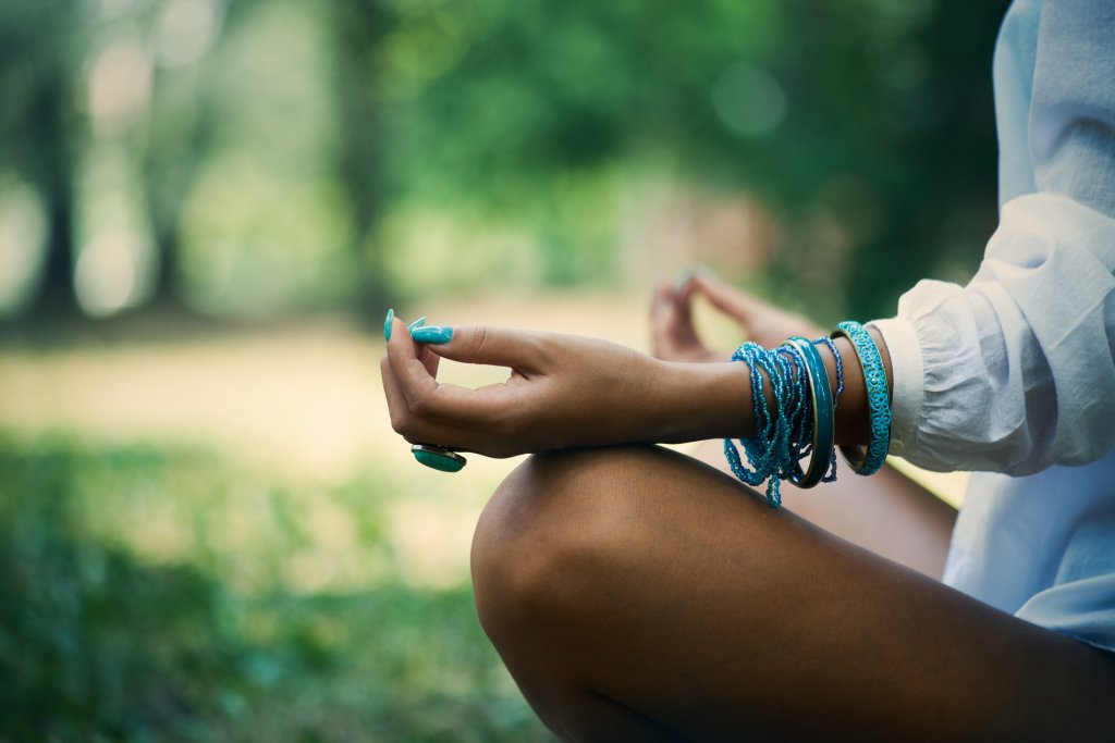 woman meditate in wood, close up of legs, hands and part of body in white shirt, selective focus on hand, side view