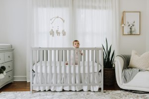 Baby in crib with decor mobile.
