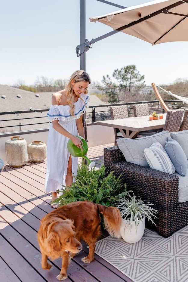 Dani Austin watering plant with dog.
