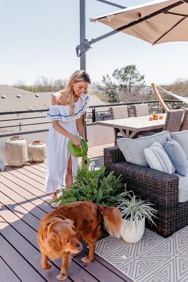 Dani Austin watering plant with dog.