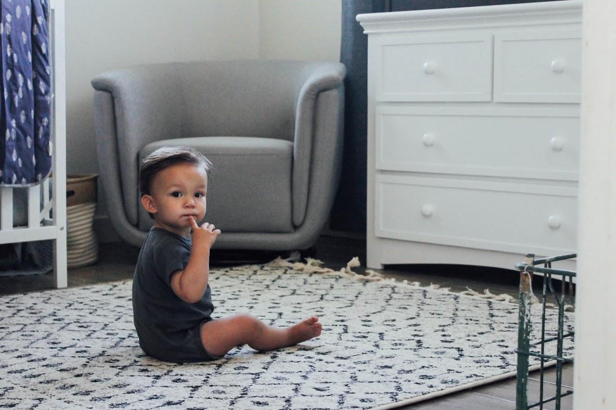 Baby sitting on rug.