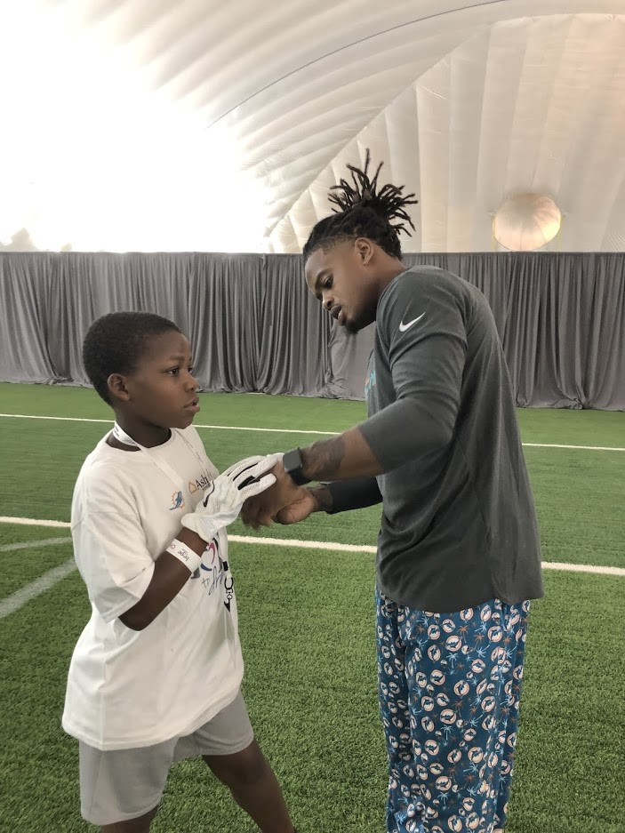 Dolphins player giving child a practice glove.