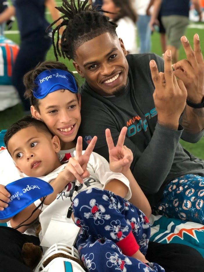 Dolphins player posing with kids in the Bubble.