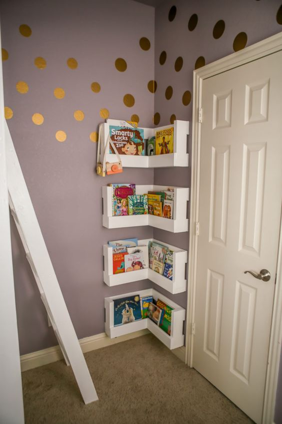 Polka dot wallpaper and behind the door wall shelves with books.